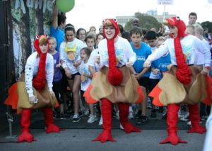 Children joyfully running dressed as turkeys during a yearly Turkey Trot